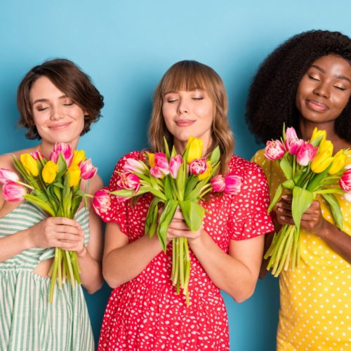 Gina Rolkowski, discusses using the 5 Pillars of Post-Traumatic Growth to demonstrate healing from Complex PTSD in action. The image shows three women in brightly colored dresses holding bouquets of tulips smiling with their eyes closed