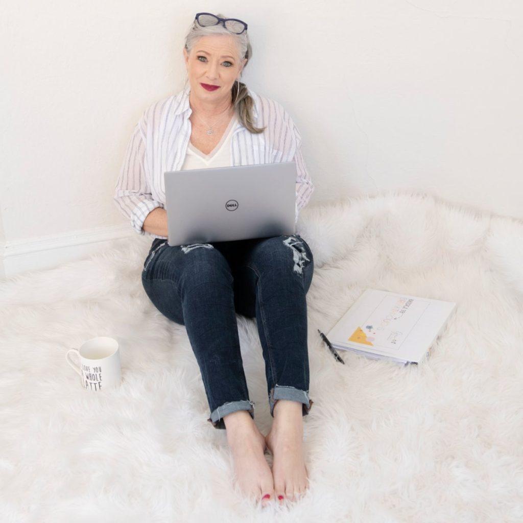 Trauma and Recovery Coach Gina Rolkowski sitting on fuzzy white rug