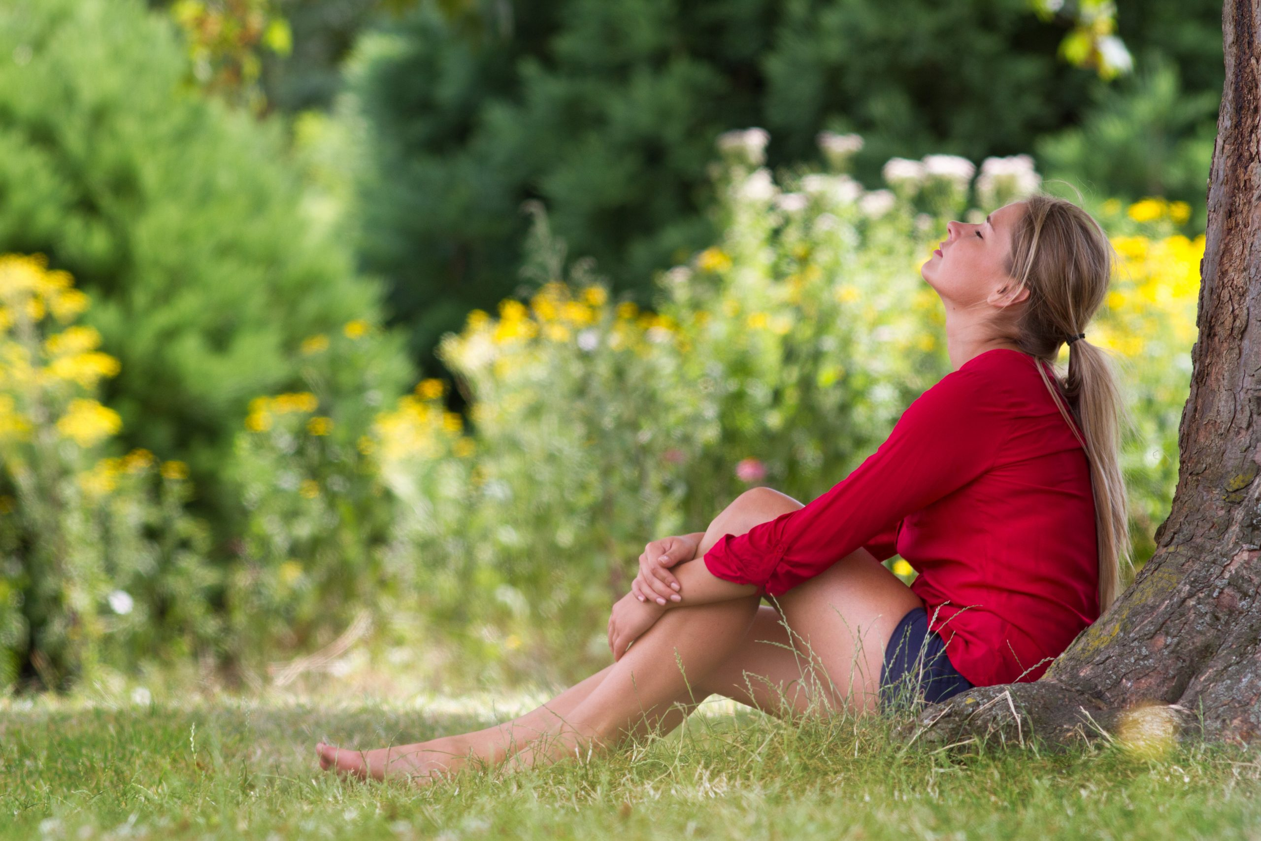 Gina Rolkowski shares how to heal from childhood trauma by getting out of your mind and noticing how your body expresses your feelings. Image shows a young woman wearing shorts and a red sweater under a tree with her eyes closed.